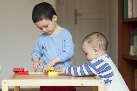 Twee kinderen, kleine peuter of een baby kind en zijn oldrer broer, die samen thuis spelen met bouwstenen op een lage tafel.