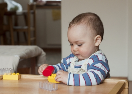 Baby or toddler child playing with plastic blocks at home.