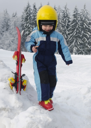 Portrait of a cute happy child skier, boy or girl, with yellow skiing helmet in a winter ski resort. photo