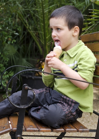 Child eating ice cream in garden, sitting on rustic wooden chair.  photo