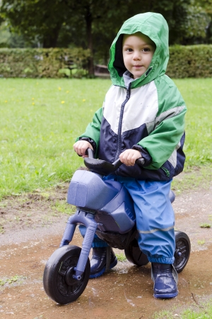 Child , a toddler boy, riding a toy bike in park on rainy day   photo