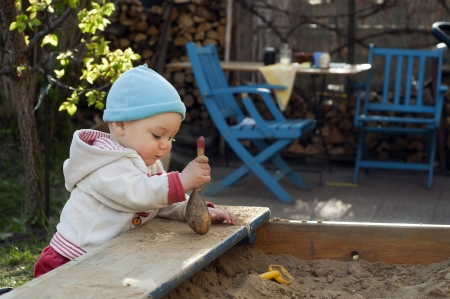Baby or toddler child playing with sand at sandpit or sandbox in a patio garden.  Stock Photo