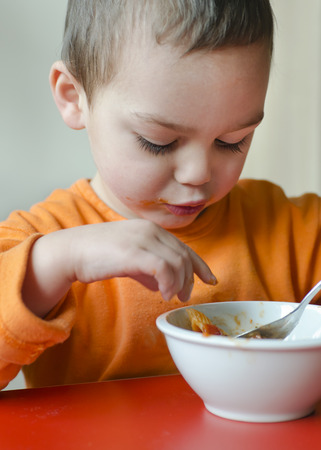 Child toddler eating pasta from a bowl at table