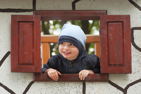Portrait of a small child in a wooden window of a play house in a playground in a park or a garden. Stock Photo
