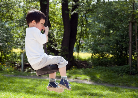 Child boy swinging on a tree swing in an outdoor adventure playground in the park. photo