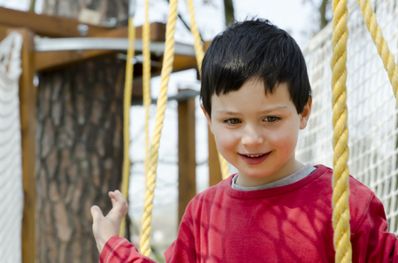 Portrait of a happy child boy at aventure playground. photo