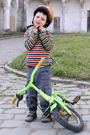 put: Child putting on a safety helmet and getting ready to cycle on his bicycle.