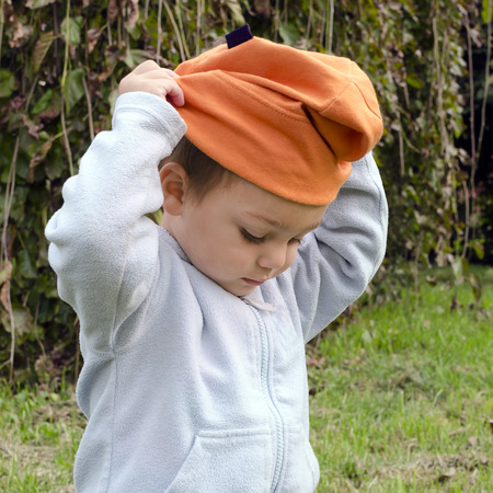 put: Child toddler trying to put on his hat or cap.