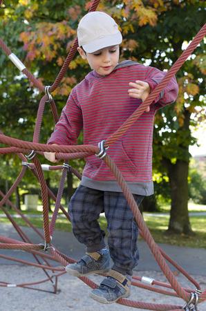 climbing frame: Bambino che gioca al parco giochi in una cornice di arrampicata corda. Archivio Fotografico