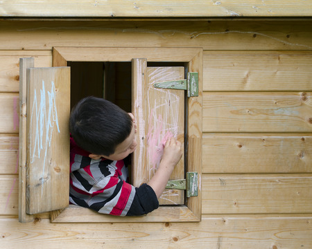Child drawing on a window shatter of a playhouse with a chalk.  photo