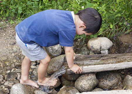 Child washing his feet at nature water stream. photo