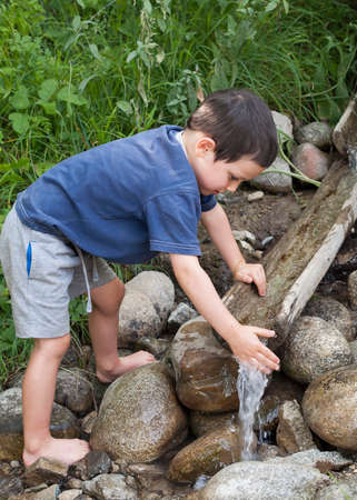 Child washing hands in water stream with wooden fountain.  photo