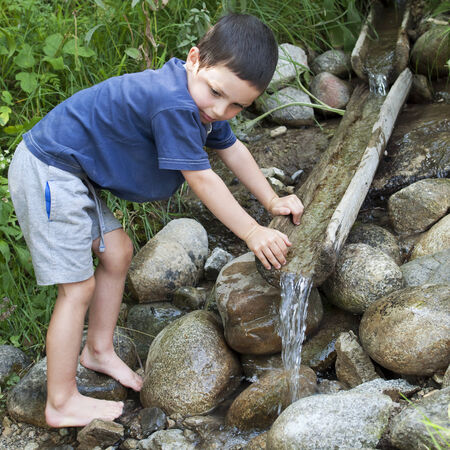 Child washing hands in nature water stream with wooden fountain.  photo