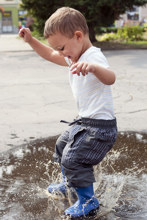 Happy child jumping into a street puddle.