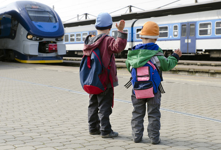Two children with backpacks waving to trains at train station, back view  Stock Photo