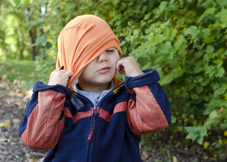 put: Child trying to put on hat, portrain in  autumn or fall park   Stock Photo