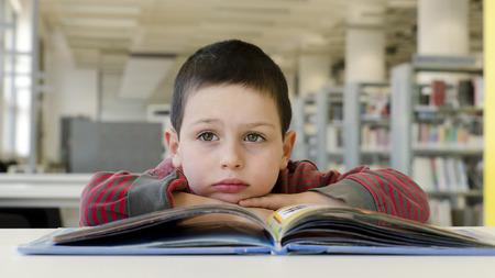 Zasněný dítě čtení kniha stůl ve veřejné místnosti knihovny. Reklamní fotografie
