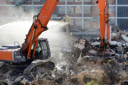 demolition: Demolition site of old factory building with heavy machines at work Stock Photo