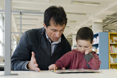 Child pupil with parent or teacher reading a book in public library.  photo