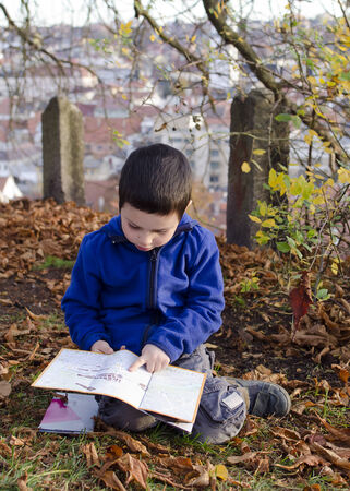 trebic: Child boy reading a map or city plan while sitting on ground