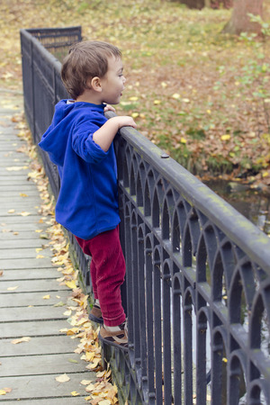 Child standing on a iron fence of a bridge photo