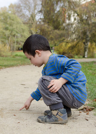 sand writing: Child boy writing into a sand on a path in a park with his finger. Stock Photo