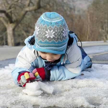street kid: Child toddler playing with last snow and ice  in early spring. Stock Photo