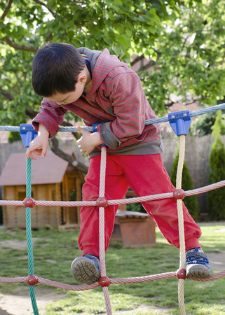 obstacle course: Child playing at children playground, climbing on  rope ladder obstacle course equipment.