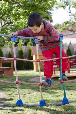 obstacle course: Child palying at children playground, climbing on  rope ladder obstacle course equipment. Stock Photo