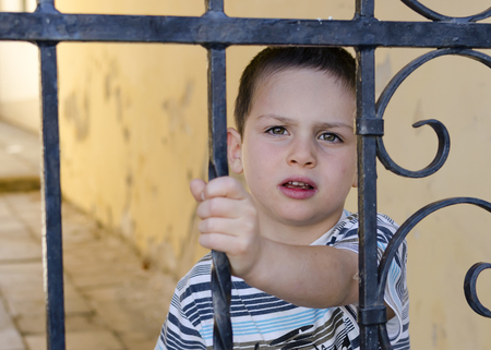 street kid: Child behind the iron fence or gate in steet of a town or city.