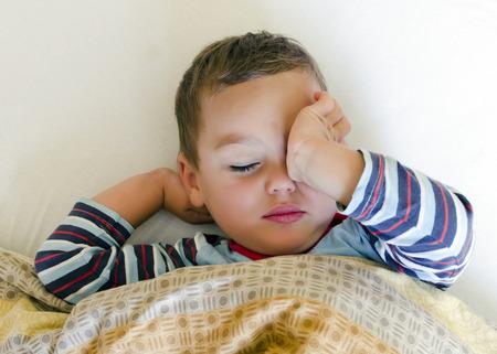 levantandose: Sleepy niño en la cama despierta o conseguir un sueño.
