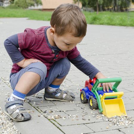 carritos de juguete: Muchacho del niño niño que juega con un coche excavadora de juguete de plástico.