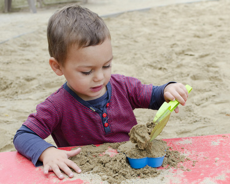 sandpit: Child toddler, boy or girl, playing in sandpit with plastic toys.