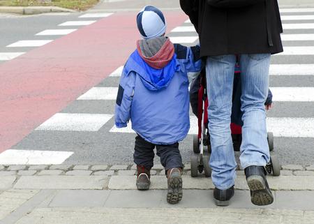 Padre con el niño y el coche cruzando la carretera en un cruce de cebra peatonal. Foto de archivo