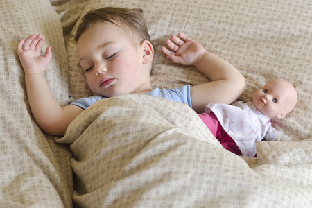 Portrait of toddler child sleeping in a bed with a toy doll. photo