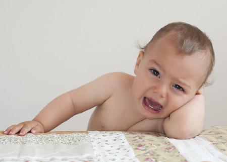 Pianto bambino piccolo bambino, ragazzo o ragazza, a casa appoggiato sul letto.