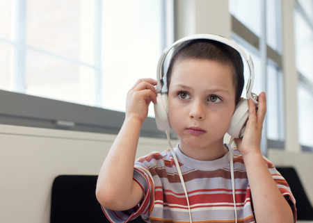Child boy with headphones listening music or audio in a classroom or library room 스톡 콘텐츠