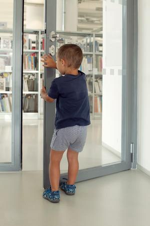 abriendo puerta: Niño abriendo una puerta y entrar en la habitación de la biblioteca pública o escolar.