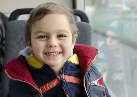 Portrati of a happy smiling child traveling on public trasport bus. Stock Photo