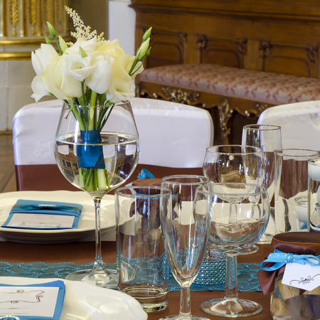 floral arrangements: Wedding table setting arrangement in a luxury restaurant with white rose bouquet.