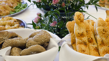 bread basket: Bread rolls or stick on a wedding or party table with flowers or floral decoration.