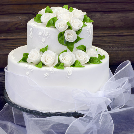 marzipan: Wedding cake with white frosting or icing decorated with white roses and green leaves.