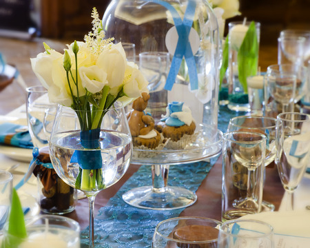 Wedding table setting arrangement in a luxury restaurant with white rose bouquet.