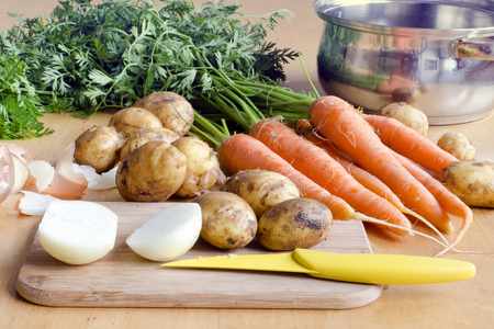 Raw carrot, new potatoes and onion  vegetable on a table ready for soup. photo