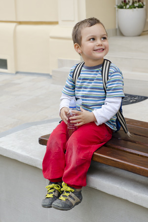 Happy smilling child  sitting on a bench holding a bottle of water. photo