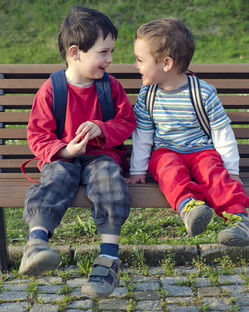 Two children boys, friends or brothers sitting on a bench, talking and laughing.