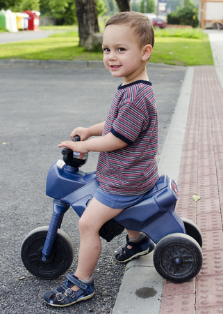 residential street: Child toddler playing riding a toy bike at a residential street with pavement. Stock Photo