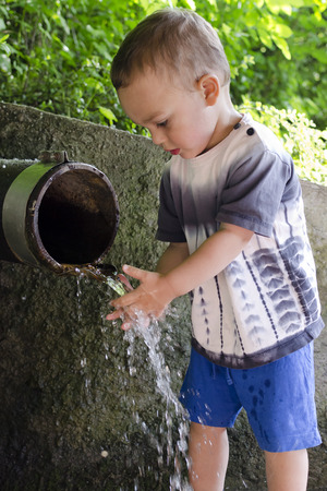 Child washing hands and playing with water at rustic pipe with running drinking water, aid concept.