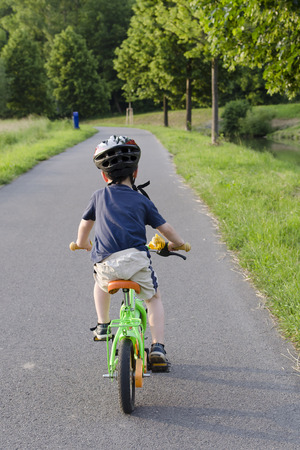 Child cycling on a cycle path in nature, back view.
