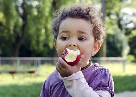comiendo frutas: La muchacha del niño que come una manzana en un parque de la naturaleza.